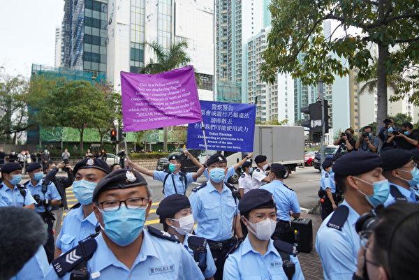 Cảnh sát Hong Kong giơ cờ xanh và cờ tím cảnh báo công dân bên ngoài tòa án Tây Cửu Long chiều ngày 1/3. (Yu Gang / The Epoch Times)