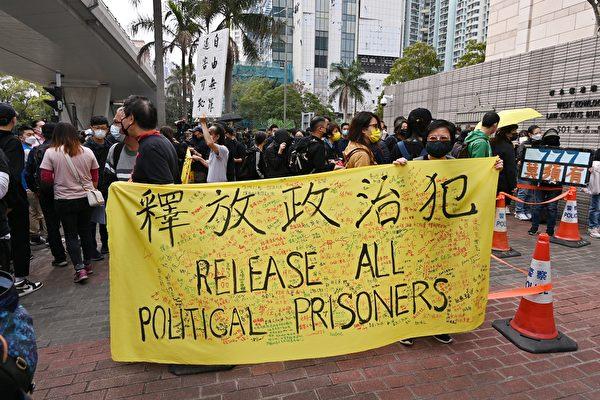 """Sáng 1/3, người dân Hong Kong tập trung trước cửa tòa án Tây Cửu Long và giơ biểu ngữ với dòng chữ """"Thả tất cả tù nhân chính trị"""" để bày tỏ sự ủng hộ tới 47 nhà dân chủ bị chính quyền Hong Kong khởi tố hôm 28/2. (Song Bilong / The Epoch Times)"""