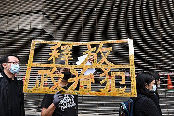 3月1日上午,香港47名泛民主派人士在西九龍裁判法院提堂。法院外有市民拿著「釋放政治犯」的標語表示抗議、聲援。(宋碧龍/大紀元)