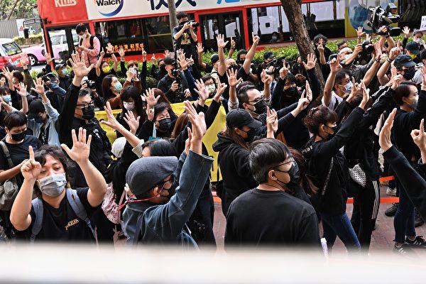 """Người dân Hong Kong giơ ngón tay """"5 và 1"""" trước cửa tòa án Tây Cửu Long để bày tỏ """"5 yêu cầu lớn, 1 cũng không thể thiếu"""". (Song Bilong / The Epoch Times)"""