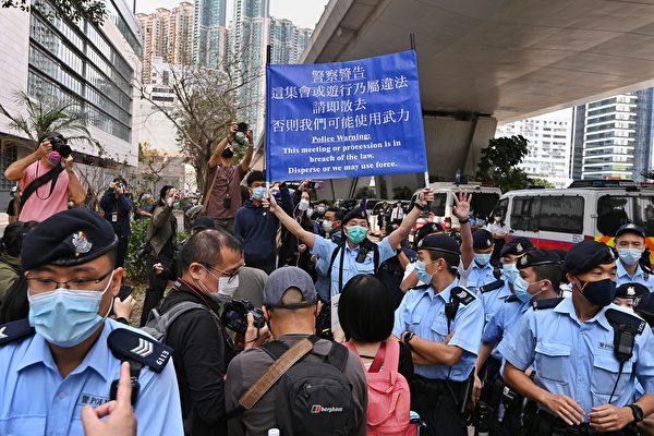 Cảnh sát Hong Kong giơ cờ xanh cảnh báo công dân bên ngoài tòa án Tây Cửu Long chiều ngày 1/3. (Song Bilong / The Epoch Times)
