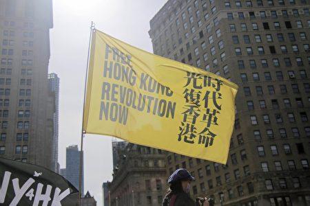 """民眾在紐約市曼哈頓弗利廣場公園手舉""""光復香港 時代革命""""旗幟。"""