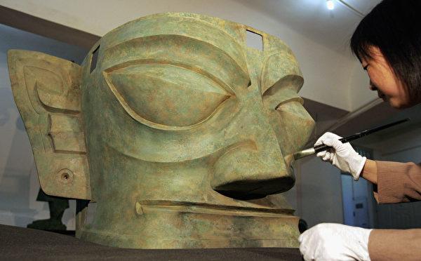 2005年4月13日,考古人员正在复原从三星堆遗址挖掘出来的青铜造像,与中国传统历史的印记完全不同。(China Photos/Getty Images)