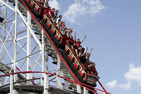 图为2005年5月29日,纽约民众乘坐月亮公园内的旋风过山车(Cyclone roller coaster)。