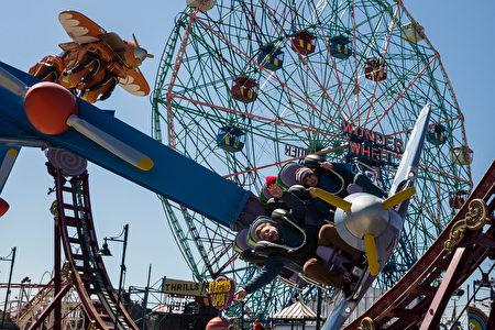 图为2005年5月29日,纽约民众乘坐月亮公园内的滑翔机(Hang Glider)游乐设施。