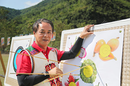 卑南乡乡长许文献举弓射向特别制作的水果靶纸,祈求五果开运,疏解干旱。