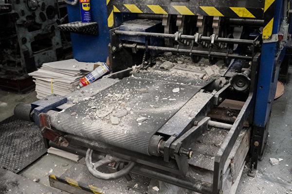 Sau khi dùng búa phá huỷ, nhóm côn đồ còn rắc bột đá hỗn hợp lên máy xuất báo. (Yu Gang / The Epoch Times)