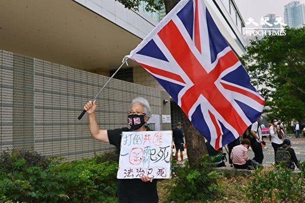 """4月16日,香港""""8.18集会""""与""""8.31集会""""案进行宣判程序。香港王破皮举着英国国旗前来声援。(宋碧龙/大纪元)"""