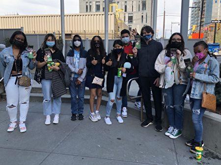 """5月2日在纽约华人社区法拉盛,一群非裔和西语裔年轻人在""""EndCCP""""倡议书上签名。"""