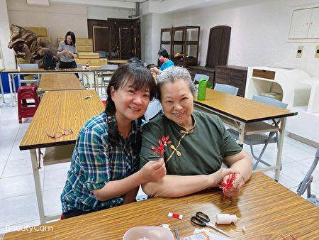 学员吕玉琴,展示她亲手完成的小牡丹春仔花胸针,右为施丽梅。