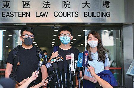 """前香港众志秘书长黄之锋等人因参加""""六四""""烛光晚会,遭港警以未经批准集结罪逮捕。香港法院6日宣判,黄之锋等人被判刑4到10个月不等。图为资料照,黄之锋(中)。"""