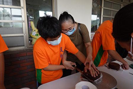 春晖志工手把手,辅导民和国中慈辉分校学生将蛋糕切半。
