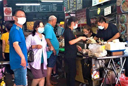 市场门口知名萝卜糕店的排队人龙不见了,客人点餐多数都把口罩戴紧紧。