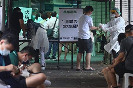 万华区快筛站 持续有民众前往筛检,医护人员落实消毒防疫工作。