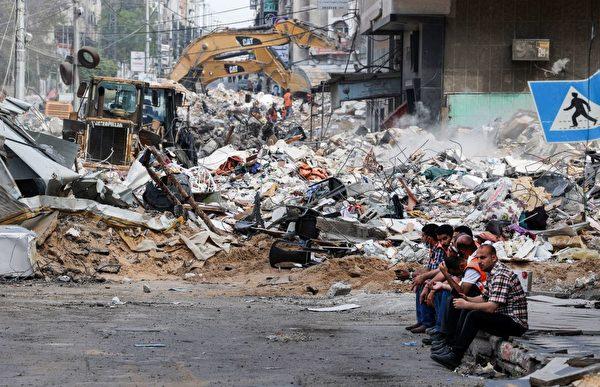 5月16日,以色列對哈馬斯控制的加沙空襲後,挖掘機正在清理被毀的建築物廢墟。(Mahmud Hams/AFP via Getty Images)