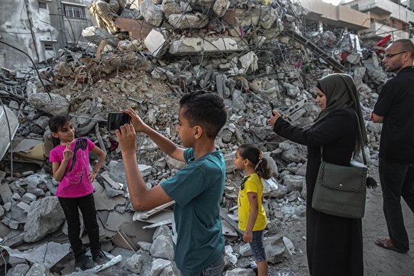 5月21日,以巴停火后,一个小女孩在加沙被毁坏的建筑物废墟前拍照。(Fatima Shbair/Getty Images)