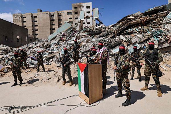巴以停火後,5月23日,巴勒斯坦的蒙面軍事人員才故意公開在廢墟前露面宣傳。(Emmanuel Dunand/AFP via Getty Images)