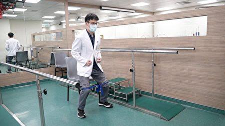 天晟医院复健科物理治疗师示范站姿开腿(弹力带)。