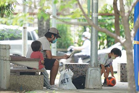 圖為家長帶著孩子外出透氣,戴上口罩防疫。