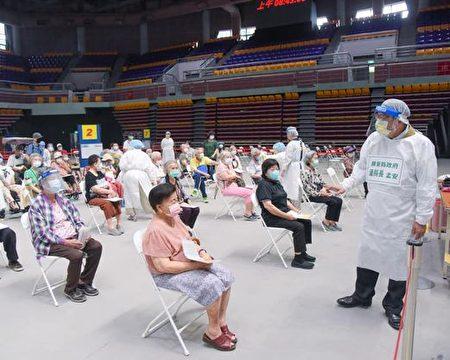 县长潘孟安(右)穿上防护衣关心接收疫苗施打的长者。
