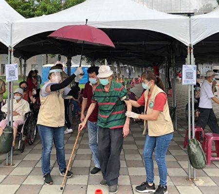 屏东县大规模疫苗施打首日,社工员在下车处为长者撑伞,协助快速通关,让家属和长辈都备感亲切。