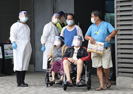 长辈由家人扶持或坐着轮椅,前往各地区接种站施打疫苗。