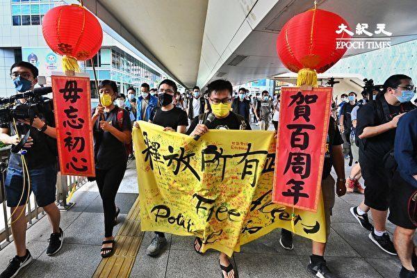 """7月1日,香港社民连4名成员按往年惯例举行游行,促请当局释放所有""""政治犯""""。图为社民连游行到达湾仔天桥上。(宋碧龙/大纪元)"""
