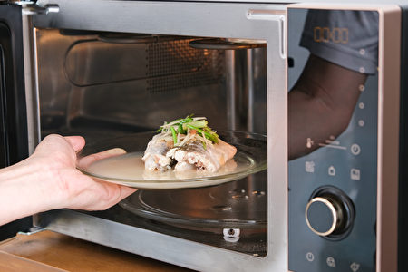 A,Housewife,Steaming,Fish,In,A,Microwave,Oven,For,A