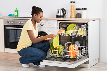 Happy,Young,Woman,Arranging,Plates,In,Dishwasher,At,Home