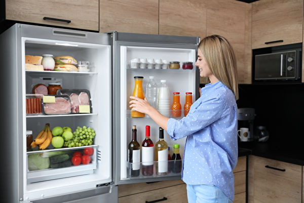 Woman,Taking,Bottle,With,Juice,Out,Of,Refrigerator,In,Kitchen