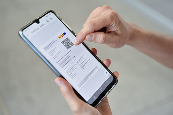 2021年7月1日,一名妇女在巴塞罗那的埃尔普拉特机场查看手机上的欧盟数位Covid-19证明。(PAU BARRENA/AFP via Getty Images)