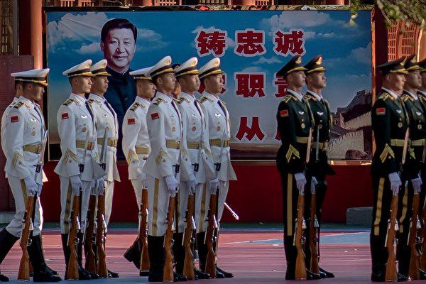2020年10月22日,中共準備紀念朝鮮戰爭前夕,中共儀仗隊士兵在北京紫禁城外的習近平畫像旁。中共軍隊僅聽命於中共最高領導人。(Nicolas Asfouri/AFP via Getty Images)
