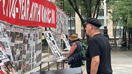 7月11日,人们在纽约市曼哈顿第五大道认真观看清算中共百年反人类罪图片展。