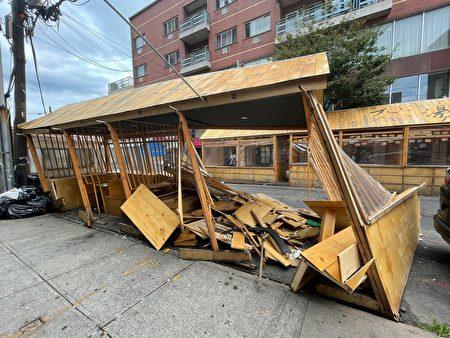 法拉盛九湯屋的四個戶外用餐隔間被汽車撞毀嚴重,整個結構明顯傾斜變形,地上有一堆斷裂的木板。