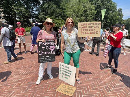 市民阿莱娜(Alena)(右)带着自己制作的三个标语来到现场。