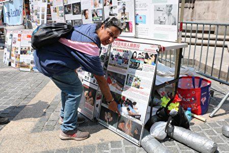 参加游行集会的马丁内斯(Dinick Martinez)看了中共罪行图片展后,最受触动的是法轮功学员受迫害的画面,他指着这幅烙烫酷刑的图片,神情严肃。