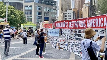 7月24日,揭露中共百年反人类罪行图片展在纽约市曼哈顿的中央公园西南角展出,吸引大批市民观看。