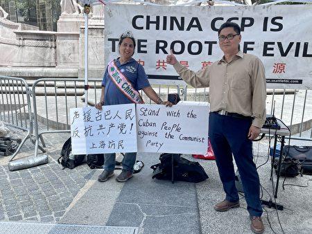 游行集会参与者马丁内斯(左)拿起这两块声援古巴人民反对共产党的标语,表示支持。邵俊(右)欢迎大家站在正义的一边。