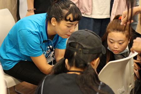 醒吾科大商設系學生江旻樺與同學認真討論資料,積極投入社團活動。
