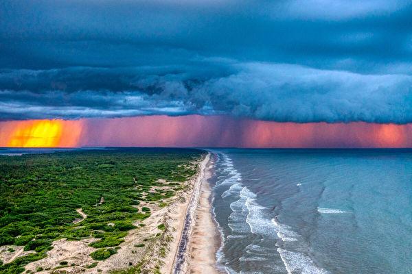 海邊落日餘輝穿過風暴雲 形成壯麗景觀
