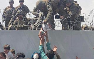 组图:阿富汗爆逃难潮 男子高举婴儿盼求生