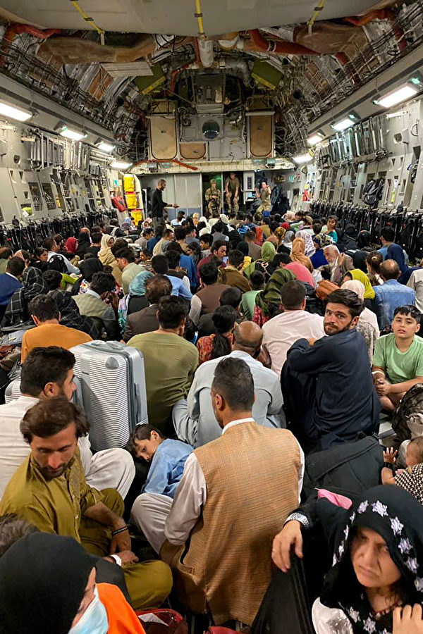 8月19日,一些阿富汗人登上一架美國軍用飛機內離開阿富汗。(Shakib Rahmani/AFP via Getty Images)