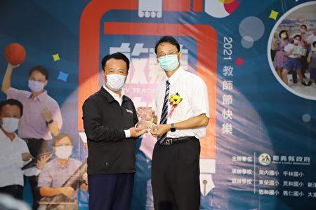 嘉义县政府22日举行教师节庆祝大会,由县长翁章梁(左)颁奖表扬今年师铎奖得主南新国小校长庄政道(右)。