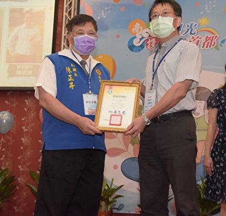 南投县副县长陈正昇(左)表扬荣获教育部师铎奖的漳兴国小校长江坤鋕(右)。