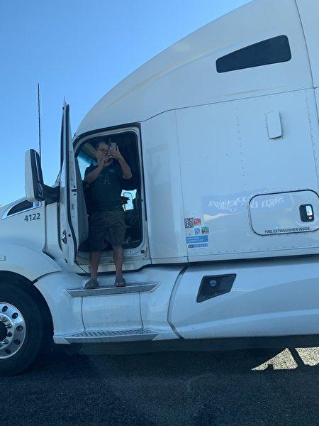 路上货车司机对着车队拍照。
