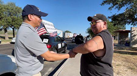 在德州Fort Stockton的公路上,皮卡司机Mario Delgedo对车队义工表示支持。